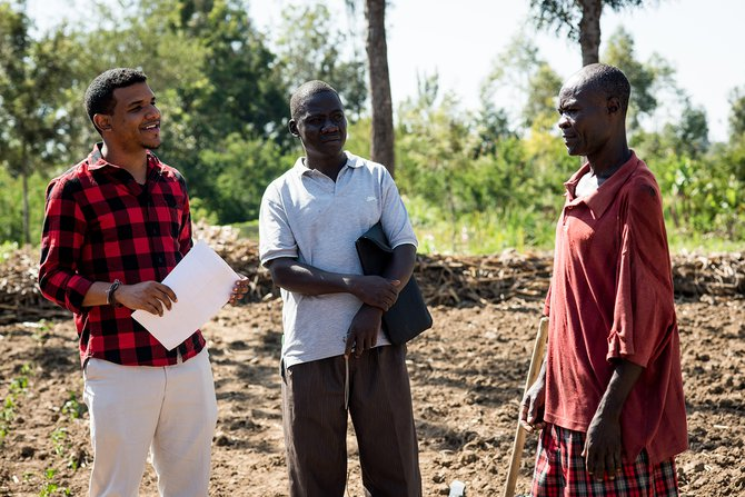 Daniel Omondi, an FO, and client discuss a seed planting trial in Kenya