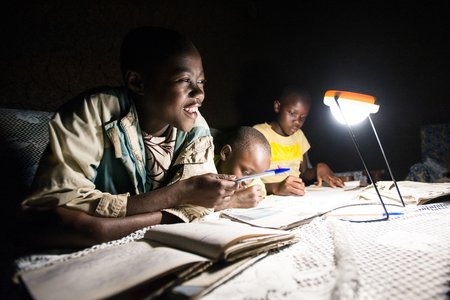 Everline Wafula's children study with the aid of a solar lamp