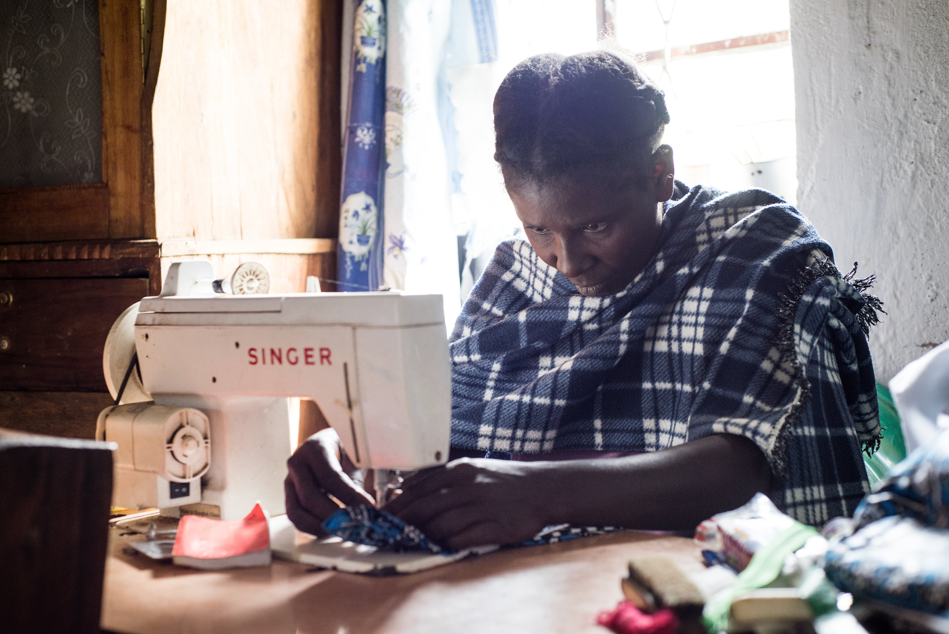 Jenipher Wasike using her sewing machine