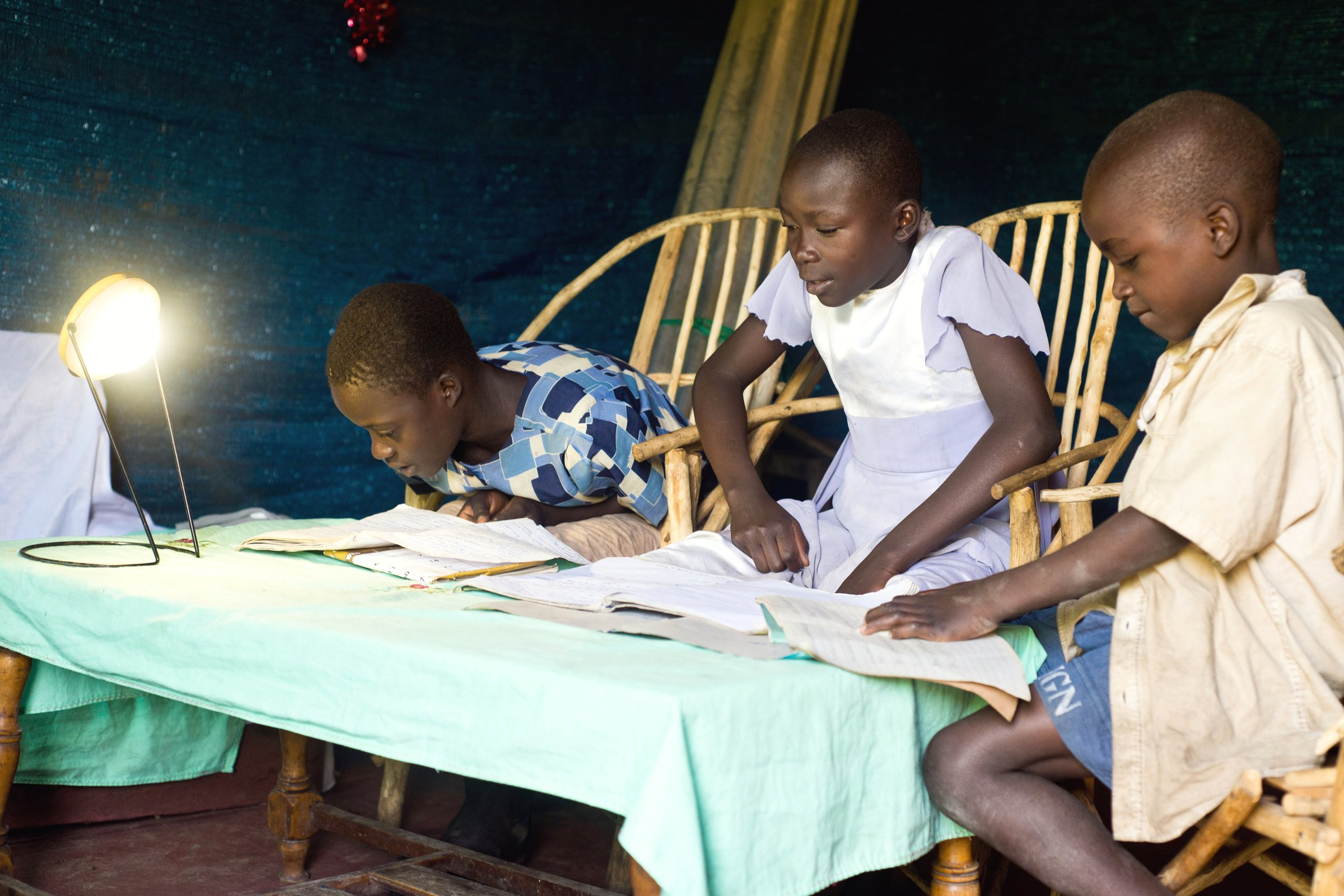 Alice Khisa and her sisters study using a solar lamp purchased from One Acre Fund on credit