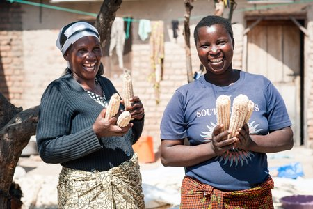 Two farmers holding maize
